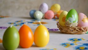 Candles made in shape of easter egg. Green, orange, yellow. Easter eggs candles and colorful Easter eggs in the stock footage