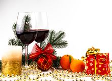 Christmas background glasses of wine on the background of a spruce branch, candles and mandarin decorations stock photos