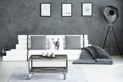 Grey modern living room. Candles on metal industrial table and grey blanket on paper couch in grey modern living room Stock Photography