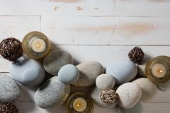 Candles and mineral pebbles for mindfulness or serenity, flat lay. Candles and mineral pebbles set on white wooden background for mindfulness, peace, ayurveda stock images
