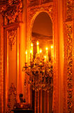 Candles and mirror at Polesden Lacey, England. Ornate chandelier and  mirror in the Saloon at Polesden Lacey stately home in England Royalty Free Stock Image