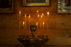 Candles near the icons. Many candles burning in a small chapel near the icons Royalty Free Stock Image