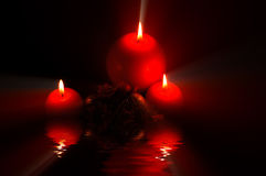 Candles by night. Three candles and christmas decoration, reflection in water Royalty Free Stock Photos