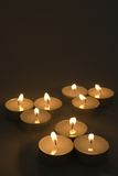 Candles in the night.. Arrangement of tea light candles burning softly against a black background.  Portrait orientation.  Copy space Royalty Free Stock Photos