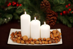 Candles and nuts on plate Royalty Free Stock Photo