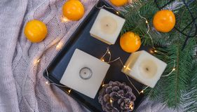 Candles, orange tangerines, pine cone on black tray and cosy fairy lights on knitte plaid backgroundand. Christmas decorations royalty free stock photo