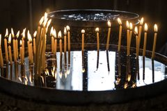 Candles in the Orthodox Church. Lighted candles during a Church prayer. The hand lit the candle in the Church Royalty Free Stock Image
