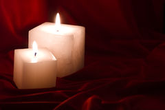 Candles over silk. Two elegant cube shaped candles over a red silk background Royalty Free Stock Photography