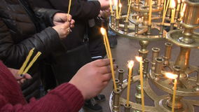 Candles and parishioners in the church of St. Petka of Bulgaria in Rupite stock footage
