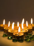 Candles and pebbles. Golden candles lighted and green pebbles Stock Photography