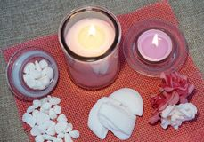 Candles, perfumed soap and other spa products. Candles, perfumed soap and other spa and wellness products on the pink jute background stock photography