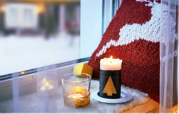 Candles and pillow on windowsill. Stock Photo