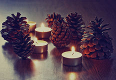 Candles and pine cones on the table Royalty Free Stock Images
