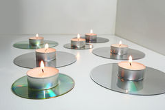 Candles placed on compact disks. Stock Photography