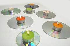 Candles placed on compact disks. Royalty Free Stock Photos