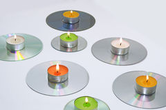 Candles placed on compact disks. Royalty Free Stock Images