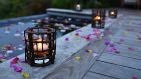 Candles on pool deck. Candles on a pool deck and flower petals all around Stock Images