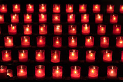 Candles in red glasses on a rack. Six rows of candles in red glasses on a rack stock images