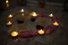 Candles red pink yellow rose petals big heart. Romantic evening, present for favorite woman man couple, candles, red pink yellow rose petals, big heart Stock Image