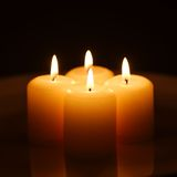 Candles with reflection. Four burning yellow candles with reflection on a white plate against dark background Royalty Free Stock Image