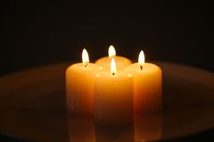 Candles with reflection on a white plate. Four burning candles with reflection on a white plate with water against dark background Royalty Free Stock Photos