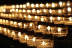 Candles of Remembrance. Warm glow from display of candles of remembrance in rows. Shallow depth of field Stock Photo