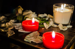 Candles and rose leaves. Three candles with rose leaves on dark background Stock Images