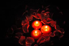 Candles with rose petals. Floating red candles and rose petals with water drops on black background Royalty Free Stock Photography