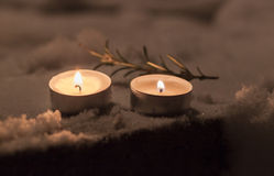 Candles with rosemary in the snow in yard Stock Photography