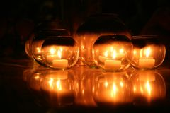 Candles in round glasses over black background. Candlelight of candles in round glasses decoration over black background Royalty Free Stock Images