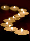 Candles in a row. Burning candles in a row, the first in focus, other blurred Stock Images
