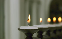 Candles in a row. Close up image of a flame from a white candle. Other candles receeding to soft focus in the background Royalty Free Stock Images