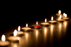 Candles in a row. On a black background Stock Photo