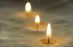 Candles on sand Stock Photography