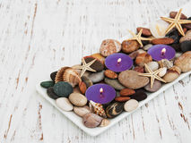 Candles with sea pebbles, starfish and sea shells Royalty Free Stock Images