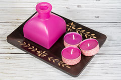 Candles set and oil bottle for spa. Studio shot of some candles and an oil bottle on wood background Royalty Free Stock Photo