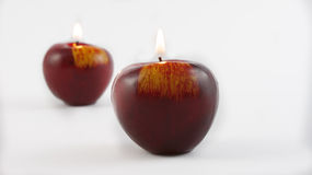 Candles in the shape of an apple. Burning candles in the shape of an apple on a white background Royalty Free Stock Photography