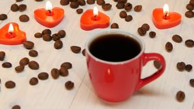 Candles in the shape of heart beside cup of coffee. Red small cup of black coffee by candlelight made for a loved one, on the white wooden table lit candles in stock footage