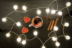 Candles in the shape of a heart, mulled wine with spices, cinnamon and anise. Rattan lanterns on black wooden table, Stock Photography
