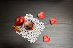 Candles in the shape of a heart, mulled wine with spices on a lace napkin, apple and cinnamon sticks. Stock Photo