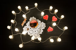 Candles in the shape of a heart, mulled wine with spices on a lacy napkin, cinnamon. Rattan lanterns on black wooden table, top vi Royalty Free Stock Photography