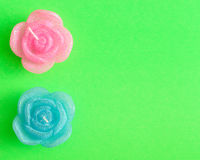 Candles in the shape of roses. On a green background Royalty Free Stock Photography