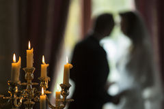 Candles and silhouette of the bride and groom at a wedding. Stock Photos