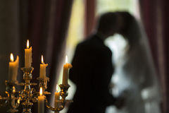 Candles and silhouette of the bride and groom at a wedding. Stock Images
