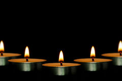 Candles. Some candles are against the dark black background Royalty Free Stock Image
