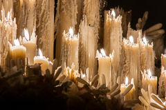 Some burning wax candles that are melted in the Holy Week of Seville. Some burning candles of wax that are melted and other candles of wax you extinguish in the Royalty Free Stock Image