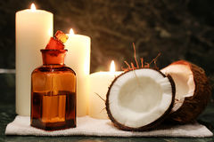 Candles spa coconut oil. White candles with a small set of soft towels and fresh coconut oil stock photos