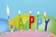 Candles spelling Happy. Happy Birthday Party Table with closeup on cake candles spelling the word, Happy royalty free stock images