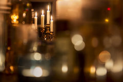 Candles. Standing brass chandelier with burning candles in shallow focus home setting Royalty Free Stock Photo