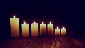Candles burning in dark. Candles standing in line burning in dark fluttering on wind, toned locked down video stock video footage